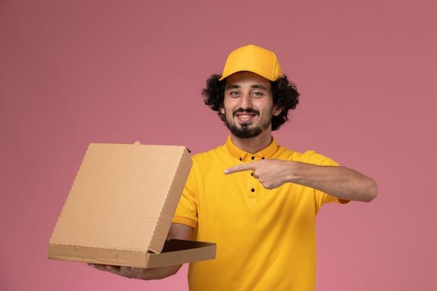 淡いピンクの壁に食品配達ボックスを保持している黄色の制服を着た正面図の男性宅配便
