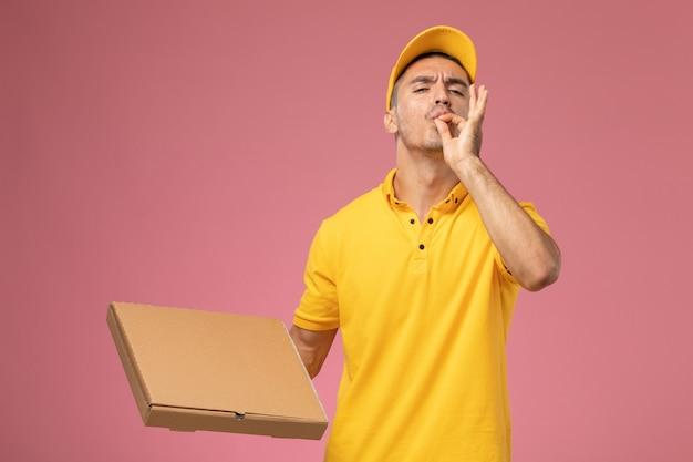 Вид спереди мужской курьер в желтой форме, держащий коробку для доставки еды, демонстрирует вкусный знак на розовом столе