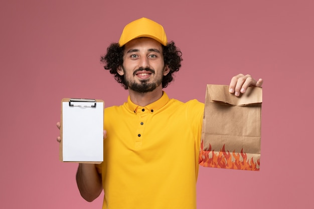 Курьер-мужчина, вид спереди в желтой форме, держит пакет с едой и блокнот на светло-розовой стене