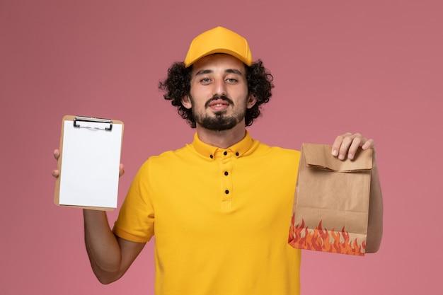 Курьер-мужчина, вид спереди в желтой форме, держит пакет с едой и блокнот на розовой стене