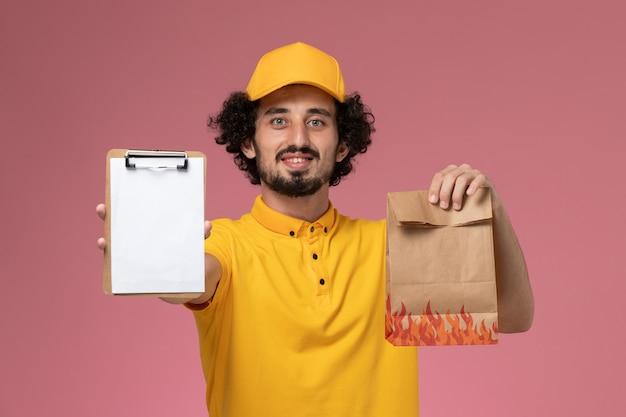 Курьер-мужчина, вид спереди в желтой форме, держит пакет с едой и блокнот с улыбкой на розовой стене