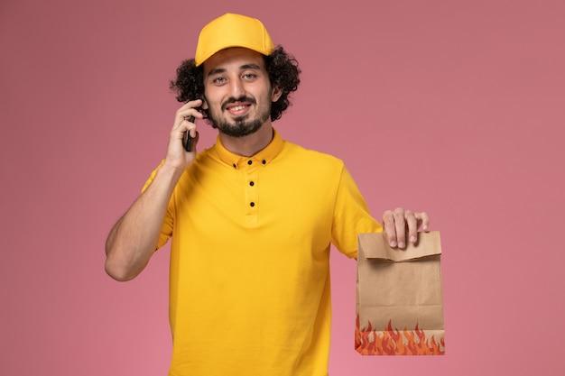 ピンクの壁に電話で話している食品パッケージを保持している黄色の制服を着た正面図男性宅配便