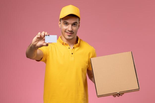 Курьер-мужчина в желтой форме с серой карточкой и коробкой для доставки еды на розовом столе, вид спереди