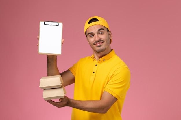 淡いピンクの背景に小さな食品パッケージとメモ帳を保持している黄色の制服を着た正面図の男性宅配便。