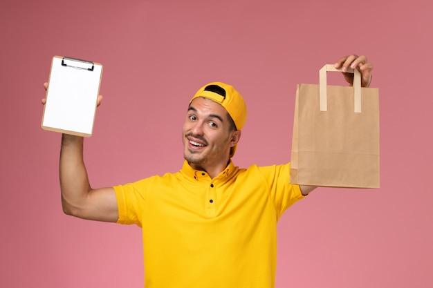 淡いピンクの背景に小さなメモ帳と配達食品パッケージを保持している黄色の制服を着た正面図の男性宅配便。