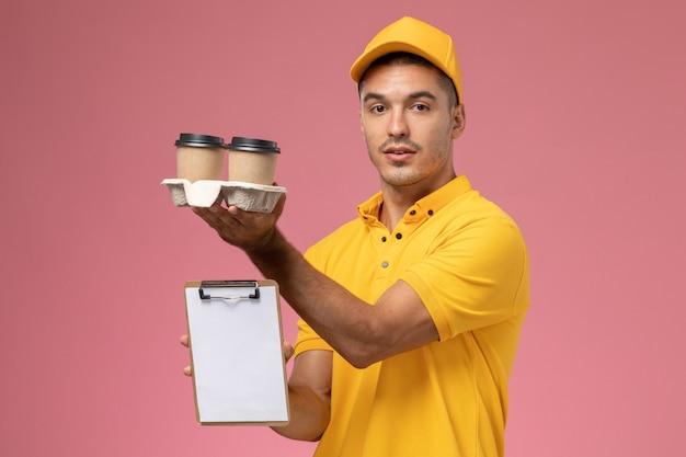 ピンクの背景にメモ帳と配信のコーヒーカップを保持している黄色の制服を着た正面男性宅配便