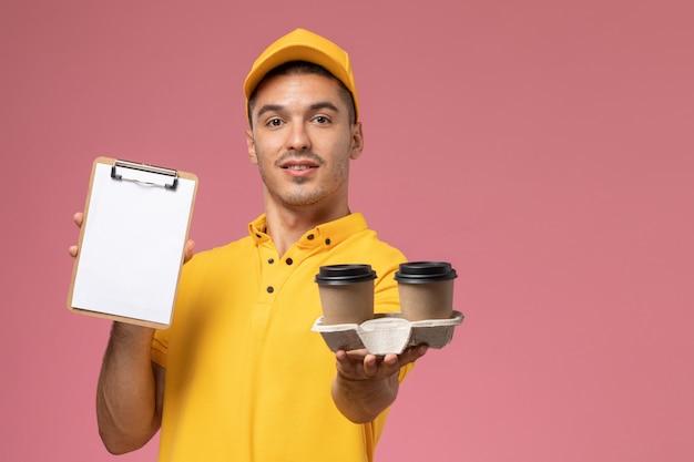 ピンクの机の上のメモ帳と配信のコーヒーカップを保持している黄色の制服を着た正面男性宅配便