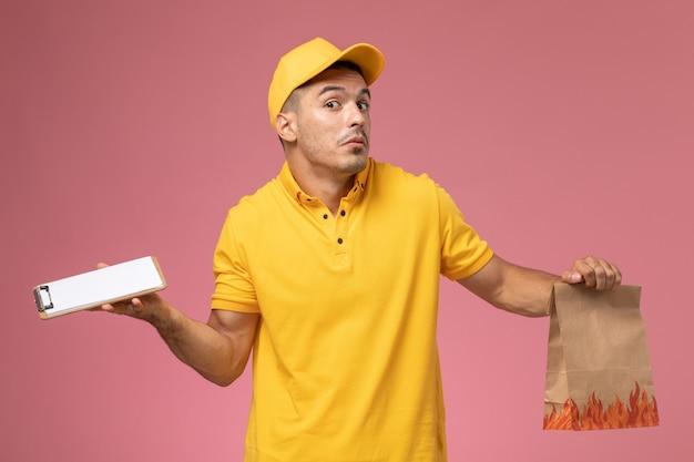 Курьер-мужчина в желтой форме, держащий блокнот и продуктовый пакет на розовом фоне, вид спереди