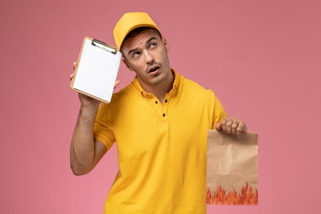 ピンクの机の上にメモ帳と食品パッケージの思考を保持している黄色の制服を着た正面男性宅配便