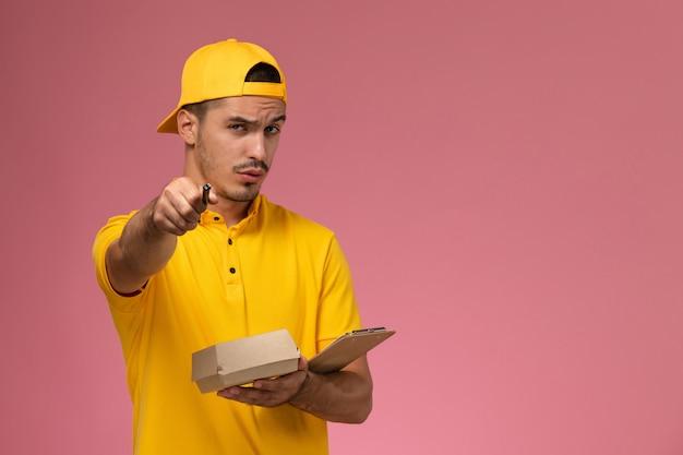 ピンクの机にメモ帳と小さな食品パッケージを保持している黄色の制服を着た正面図の男性宅配便。