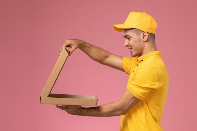 黄色の制服を保持しているとピンクの背景の食品宅配ボックスを開く正面男性宅配便