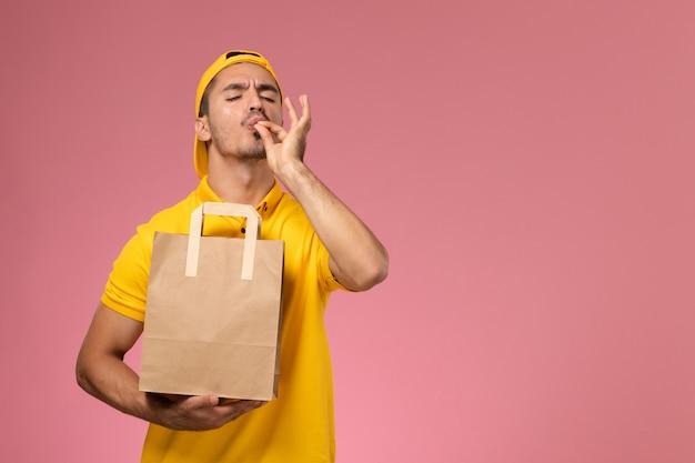 Курьер мужского пола вида спереди в желтой форме держа пакет еды доставки бумаги на розовом фоне.