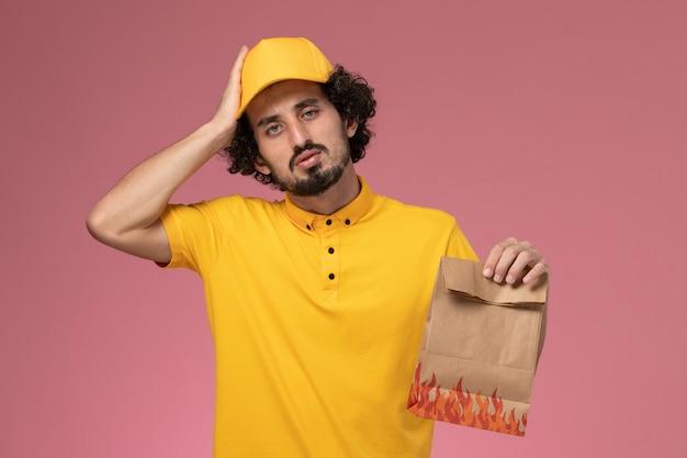 淡いピンクの壁に紙の食品パッケージを保持している黄色の制服の正面図男性宅配便