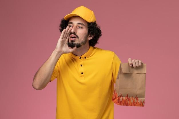 Курьер-мужчина в желтой форме, держащий бумажный пакет с едой, шепчет на светло-розовой стене, вид спереди