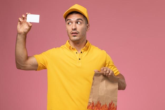 Курьер-мужчина в желтой форме, держащий белую карточку и пакет с едой на розовом столе, вид спереди