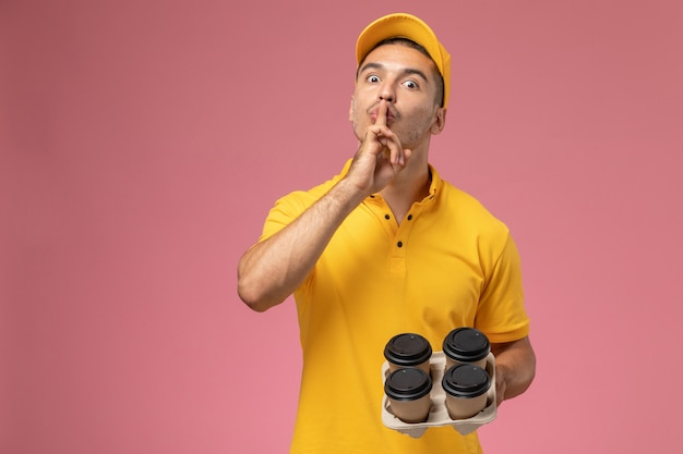 沈黙の兆しを見せ、ピンクの机の上の配達のコーヒーカップを保持している黄色の制服を着た正面男性宅配便