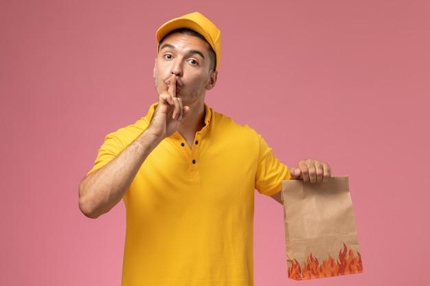 黄色の制服笑顔とピンクの背景に食品パッケージを保持している正面男性宅配便