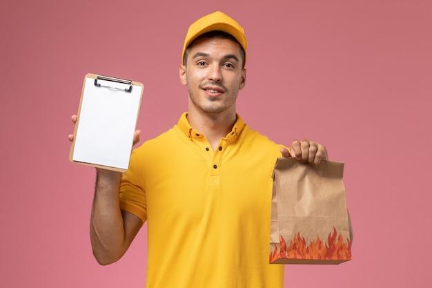ピンクの机の上のメモ帳と食品パッケージを保持している黄色の制服を着た正面男性宅配便