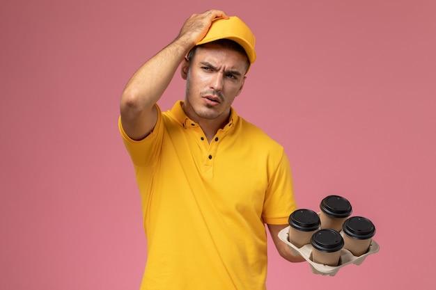 黄色の制服思考とピンクの机の上の配達のコーヒーカップを保持している正面男性宅配便