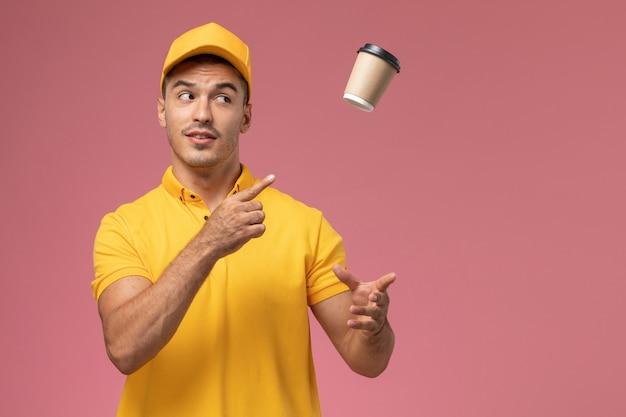 분홍색 배경에 갈색 배달 커피 컵을 던지는 노란색 제복을 입은 전면보기 남성 택배