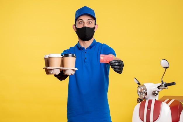 Corriere maschio di vista frontale nella maschera che tiene caffè e carta di credito sul servizio di lavoro pandemico di consegna covid dell'uniforme da lavoro gialla