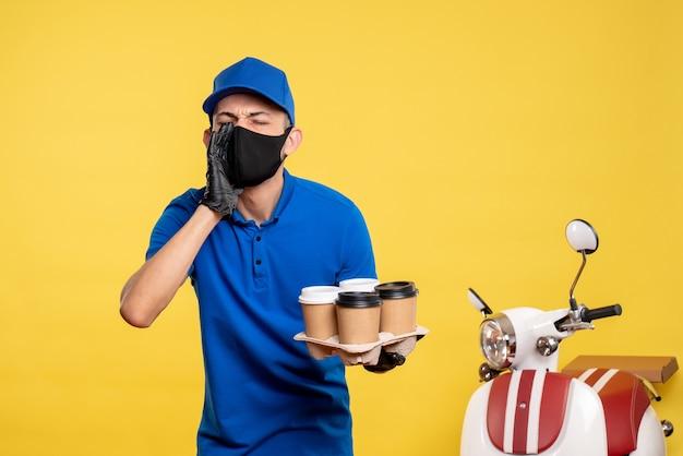 Corriere maschio di vista frontale in maschera che tiene caffè sul lavoro giallo covid-pandemia servizio consegna uniforme lavoro