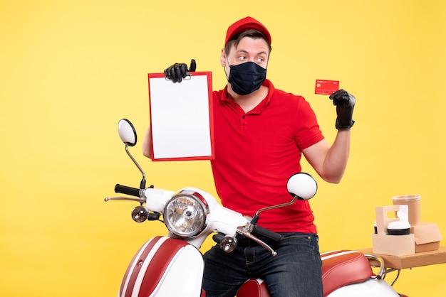 Corriere maschio vista frontale in maschera con nota di file e carta bancaria su giallo