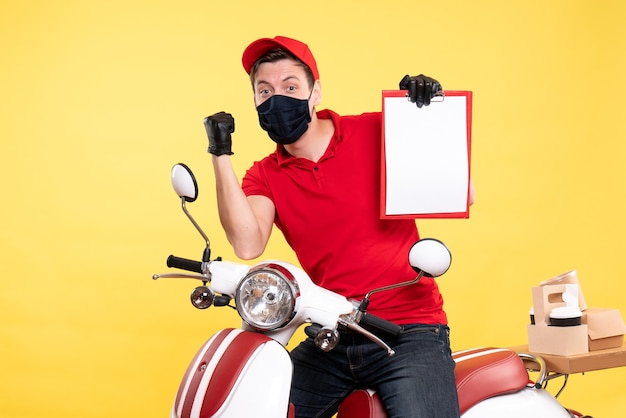 Front view male courier in mask holding file note on the yellow