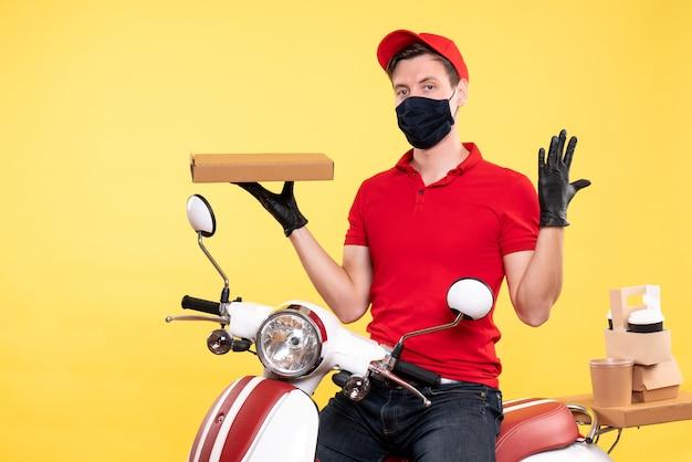 Corriere maschio vista frontale in maschera con scatola di cibo su giallo chiaro