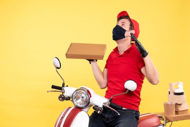Corriere maschio vista frontale in maschera con scatola per alimenti su giallo