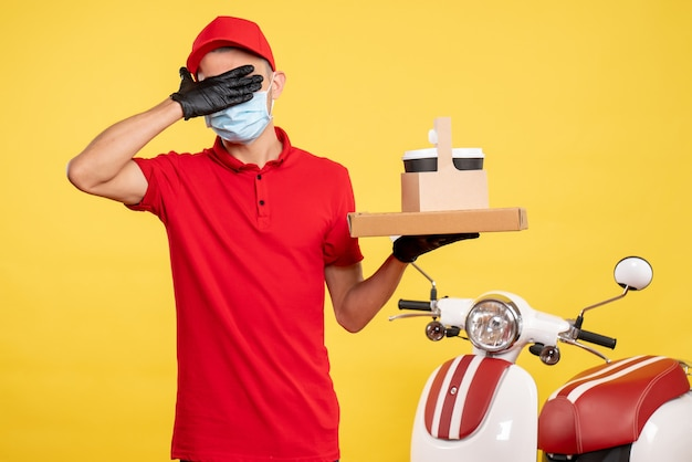 Front view male courier in mask with delivery coffee and box covering his eyes on yellow color service covid- virus job uniform pandemic work