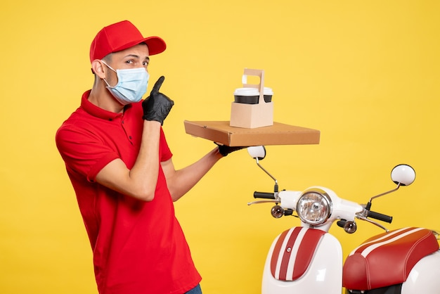Front view male courier in mask with delivery coffee and box on yellow color covid- virus job uniform pandemic work