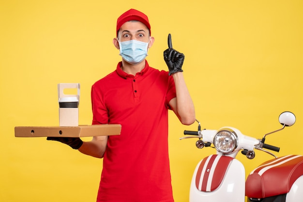 Front view male courier in mask with delivery coffee and box on yellow job color service covid- virus pandemic work uniform