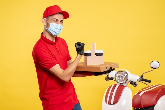 Front view male courier in mask with delivery coffee and box on yellow service covid color virus job work uniform