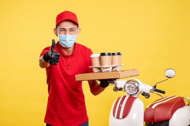 Front view male courier in mask with delivery coffee and food box on yellow service job color covid- virus pandemic work
