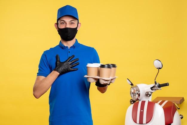 Corriere maschio di vista frontale in maschera con caffè di consegna sul lavoro uniforme di servizio di covid-servizio di consegna pandemica giallo