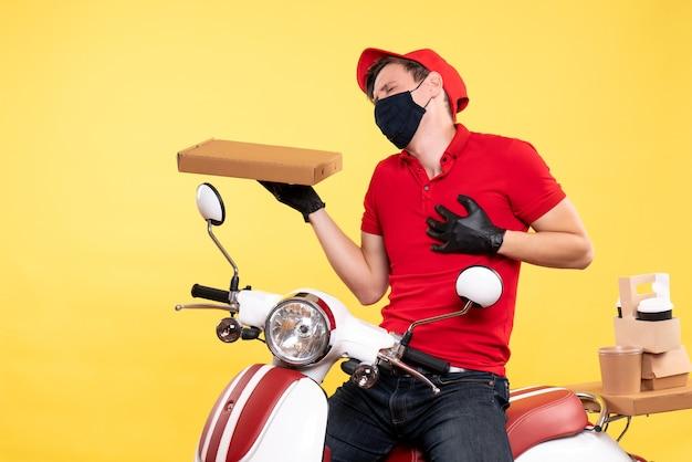 Вид спереди мужской курьер на велосипеде в маске с коробкой для еды на желтом