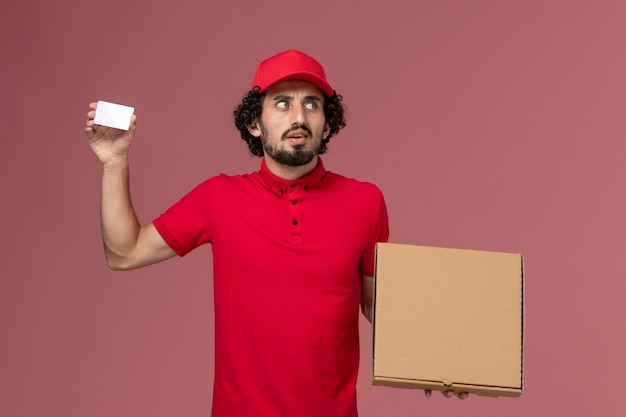 Front view male courier in red shirt and cape holding delivery food box and card on pink wall