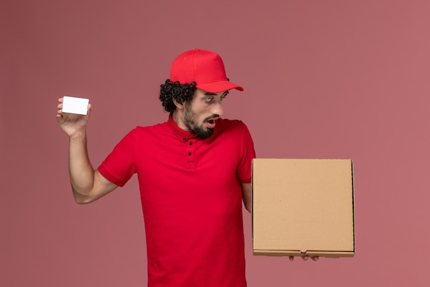 Front view male courier in red shirt and cape holding delivery food box and card on the pink wall