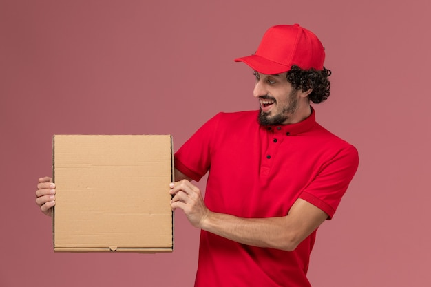 Front view male courier in red shirt and cape holding delivery food box on the light pink wall