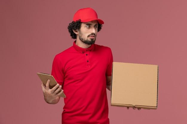Corriere maschio di vista frontale in camicia rossa e mantello che tiene la scatola di cibo di consegna e il blocco note sulla parete rosa
