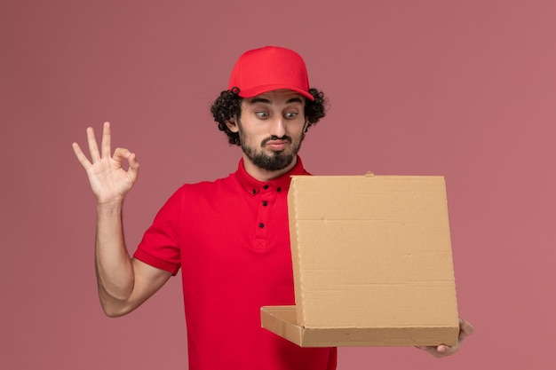 Front view male courier in red shirt and cape holding delivery food box openign it on the light pink wall