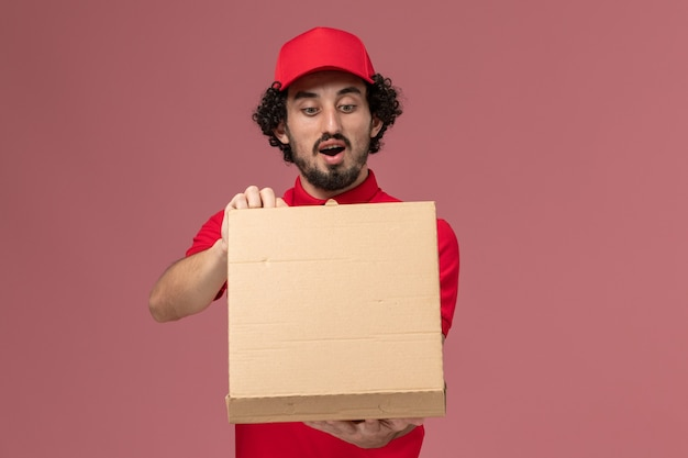 Front view male courier in red shirt and cape holding delivery food box and opening it on the light pink wall
