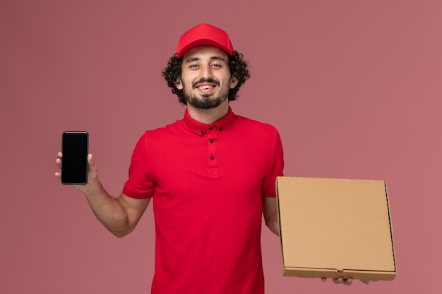 Front view male courier in red shirt and cape holding empty delivery food box with phone on pink wall