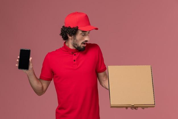 Corriere maschio di vista frontale in camicia rossa e mantello che tiene la scatola vuota dell'alimento di consegna con il telefono sulla parete rosa