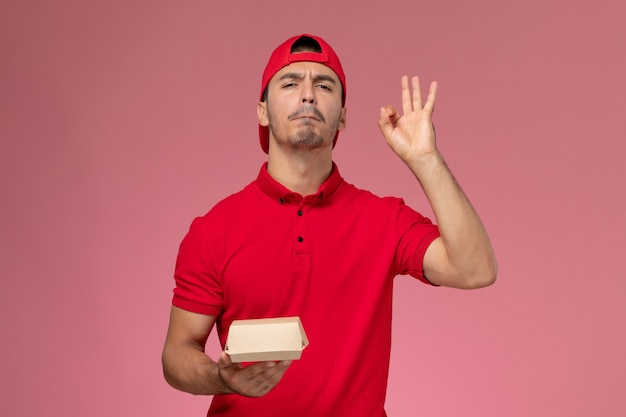 Front view of male courier in red uniform and cap holding little delivery package on pink wall