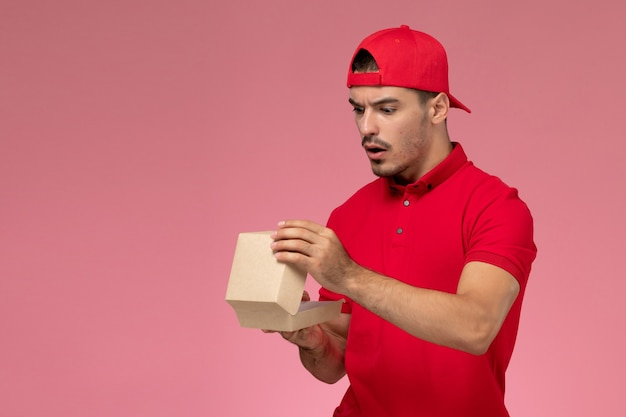 Front view of male courier in red uniform and cap holding little delivery package