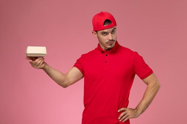 Vista frontale del corriere maschio in uniforme rossa e cappuccio che tiene piccolo pacchetto di consegna