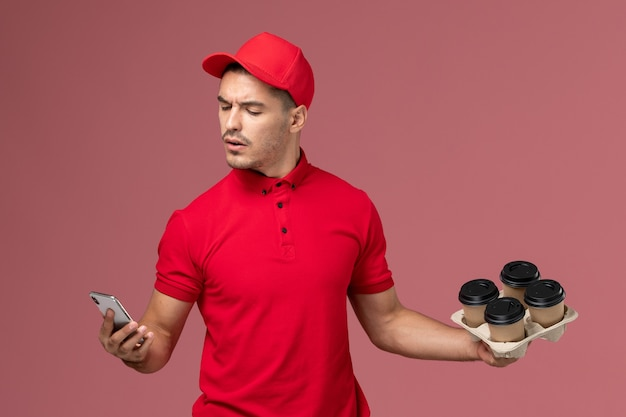Corriere maschio di vista frontale in uniforme rossa e mantello che tiene le tazze di caffè di consegna e usando il suo telefono sulla parete rosa