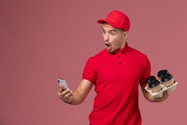 Front view male courier in red uniform and cape holding delivery coffee cups and using his phone on the pink wall